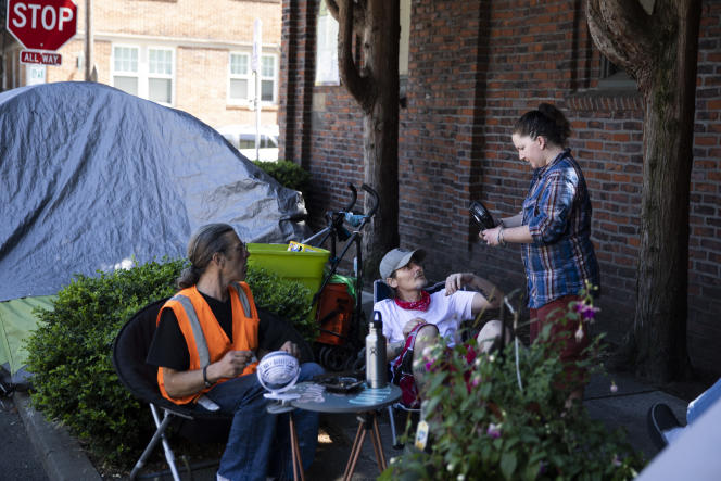 Jerry Vermillion, 57 ans, Jess, 27 ans, et son compagnon, Lokin 42 ans, à Portland, le 6 juillet 2021.M. Vermillion s'est bricolé une «résidence» et un jardin sur un morceau de trottoir, au pied de l'église Saint-Marc.