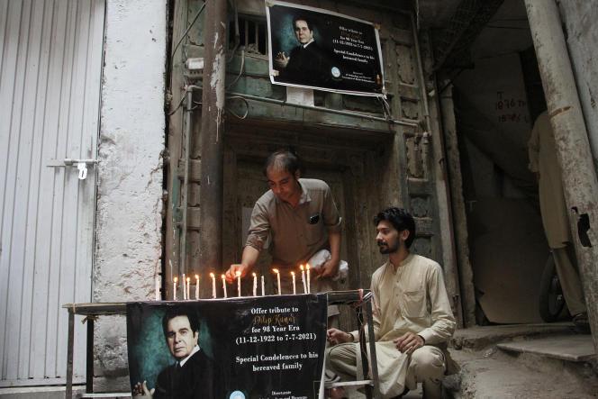 Des résidents locaux allument des bougies à côté d'un poster de l'icône de Bollywood Dilip Kumar pour lui rendre hommage, à l'extérieur des vestiges de sa maison ancestrale, à Peshawar, au Pakistan, mercredi 7 juillet 2021.
