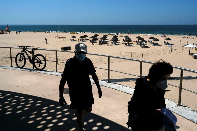 Passengers on Carcavelos Beach, Cascois Beach, Portugal on July 8, 2021.