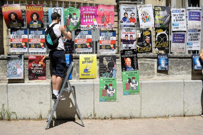 Un homme accroche des affiches de pièces dans les rues d'Avignon, le premier jour de l'édition 2021 du festival de théâtre, le 5 juillet.