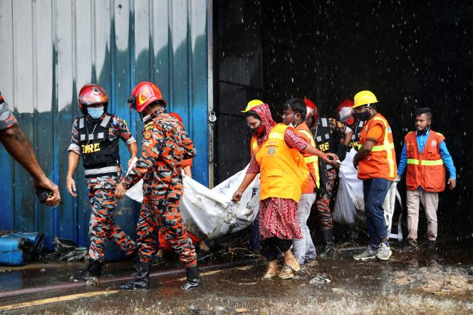 July 9, 2021 Rescue workers carry the bodies found at the burnt Hashem Foods factory near Dhaka, Bangladesh.