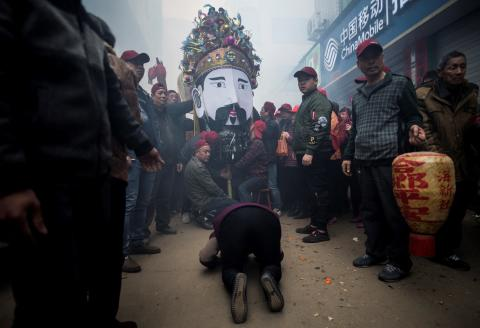 """This picture taken on March 4, 2018 shows villagers praying to a passing procession of a local Taoist sea deity in Huangqi village in China's Fujian province. - """"Possessed"""" by local gods, elaborately dressed villagers in a fishing community in eastern China are carried into the surf to ensure an abundant catch, a centuries-old rite needed now more than ever as fish stocks decline. Staged in the village of Fuye on Nanri island, """"The Dash of the Ocean Gods"""" festival is one of many visually striking traditional rituals held in Fujian province in the weeks following the Lunar New Year, which this year fell on February 16, 2018. (Photo by Johannes EISELE / AFP)"""