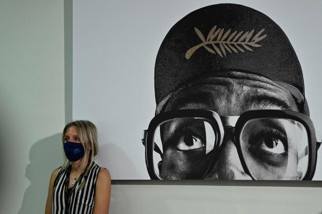 Une journaliste masquée adossée à une affiche de la 74e édition du Festival de Cannes, le 10 juillet 2021.