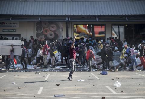 TOPSHOT - A man gestures as rioters loot the Jabulani Mall in the Soweto district of Johannesburg on July 12, 2021. South Africa said it was deploying troops to two provinces, including Johannesburg, after unrest sparked by the jailing of ex-president Jacob Zuma led to six deaths and widespread looting. Overwhelmed police are facing mobs who have ransacked stores. Six people have died, some with gunshot wounds, and 219 people have been arrested, according to a police tally issued before the army deployed. / AFP / LUCA SOLA