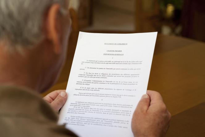 Un homme lisant un réglement de copropriété