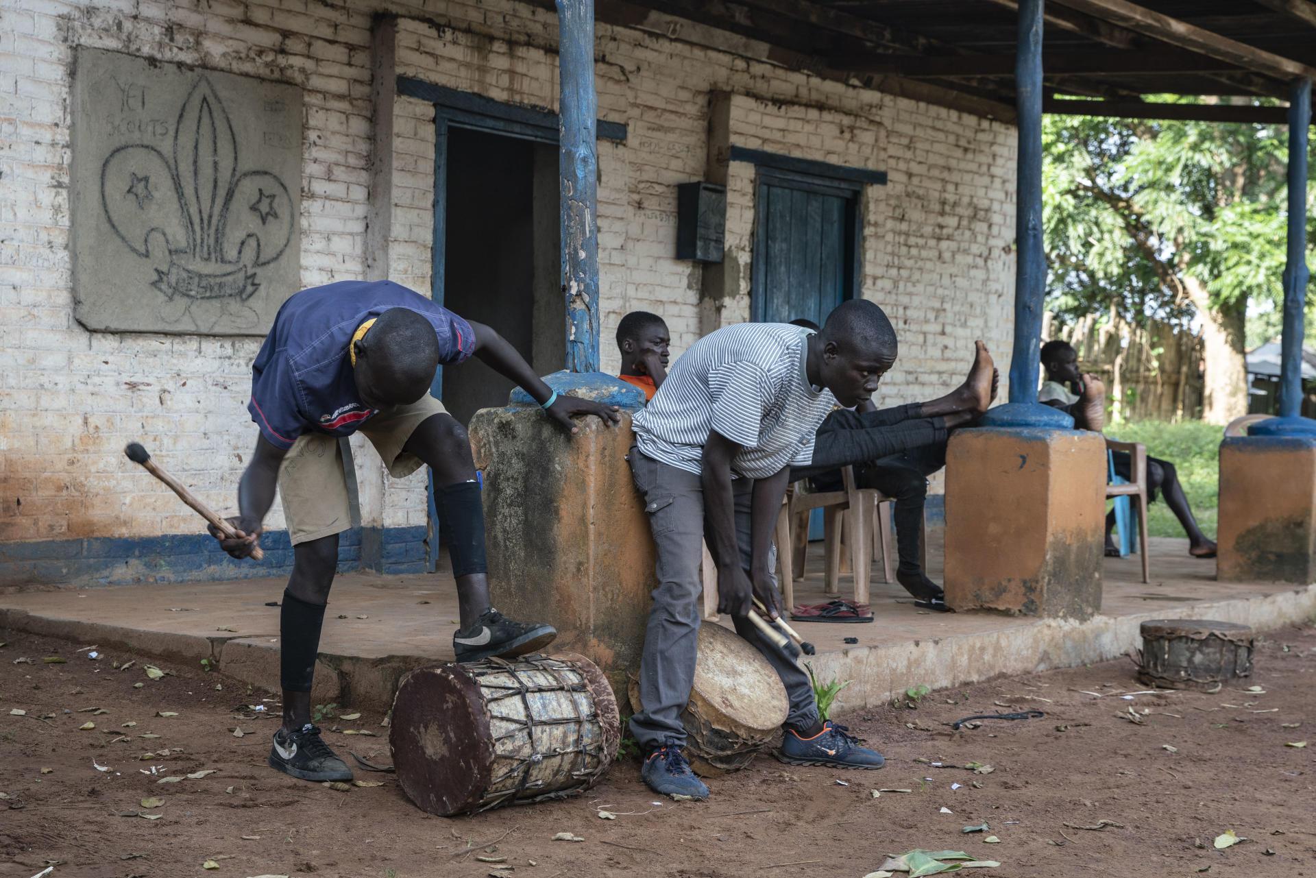 Deux jeunes hommes battent du tambour pendant les répétitions des enfants pour les préparatifs de la Fête de l'indépendance, à Yei, le 4 juillet 2021.