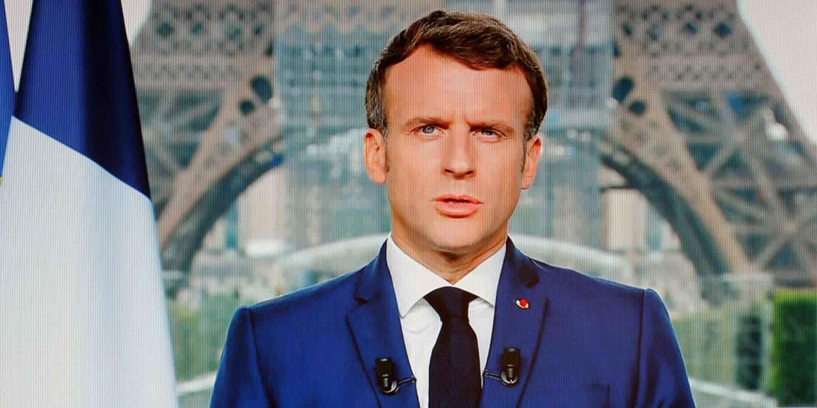 French President Emmanuel Macron is seen on a TV screen as he speaks during a televised address to the nation from the temporary Grand Palais in Paris on July 12, 2021. / AFP / Ludovic MARIN