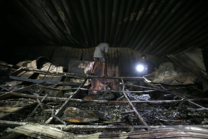 Deux personnes constatent les dégâts après l'incendie qui a ravagé l'hôpital Al-Hussein, à Nassiriya, en Irak, le 13 juillet 2021.