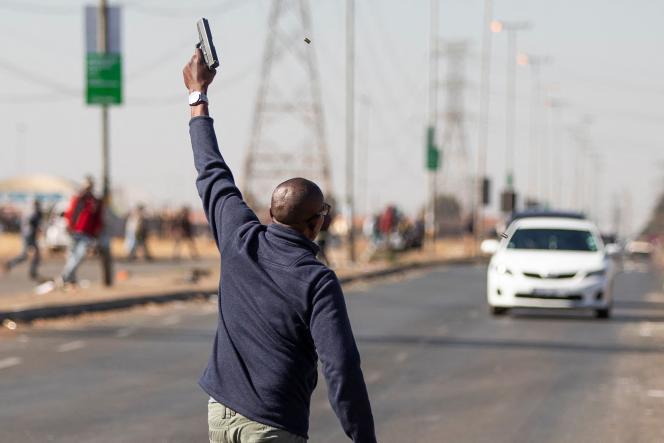 Un homme pointe une arme en l'air pour faire fuir des pilleurs présumés, à Vosloorus, à l'est de Johannesburg, mercredi 14 juillet 2021.