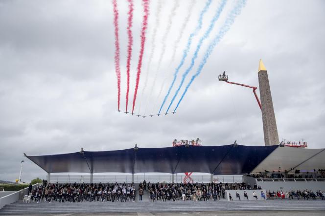La Patrouille de France survole la tribune présidentielle lors du défilé militaire du 14 juillet 2021 sur l'avenue des Champs-Elysées, à Paris.