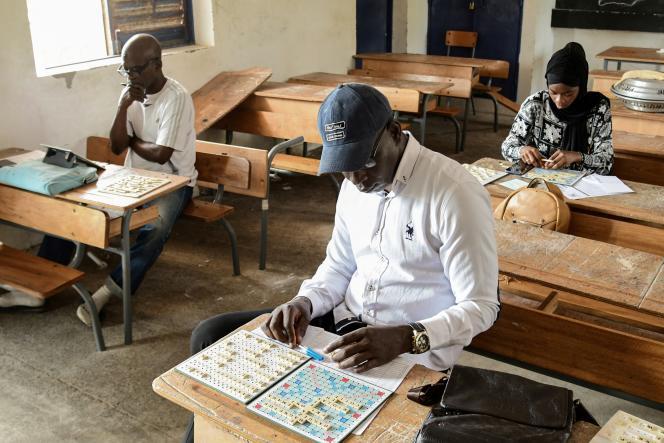 L e champion du Sénégal de Scrabble, Mouhamed Niang, avec d'autres joueurs dans une école deGuédiawaye, en banlieue de Dakar, le 3 juillet 2021.