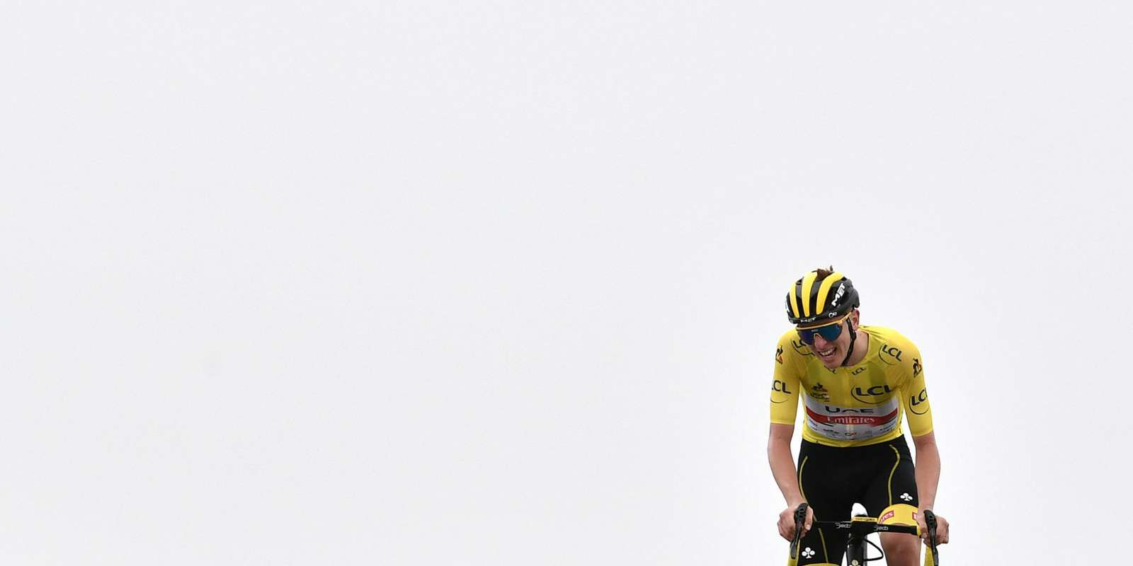 Team UAE Emirates' Tadej Pogacar of Slovenia wearing the overall leader's yellow jersey celebrates as he crosses the finish line at the end of the 17th stage of the 108th edition of the Tour de France cycling race, 178 km between Muret and Saint-Lary-Soulan, on July 14, 2021. / AFP / Philippe LOPEZ