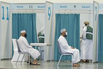 Men wait to receive a dose of the Pfizer/BioNTech Covid-19 vaccine at the Oman Convention & Exhibition Centre in the capital Muscat on June 23, 2021 during the second phase of the national immunisation plan against coronavirus. (Photo by Haitham AL-SHUKAIRI / AFP)