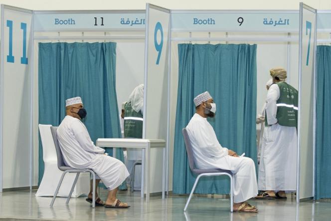 Des hommes attendent de recevoir une dose du vaccin contre le Covid-19, à Mascate, la capitale d'Oman, le 23juin 2021.