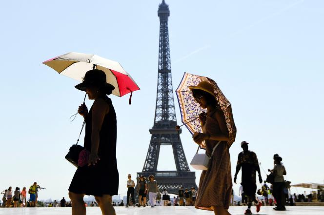 Des touristes s'abritent du soleil avec des ombrelles, sur l'esplanade du Trocadéro, à Paris, le 3 août 2018.