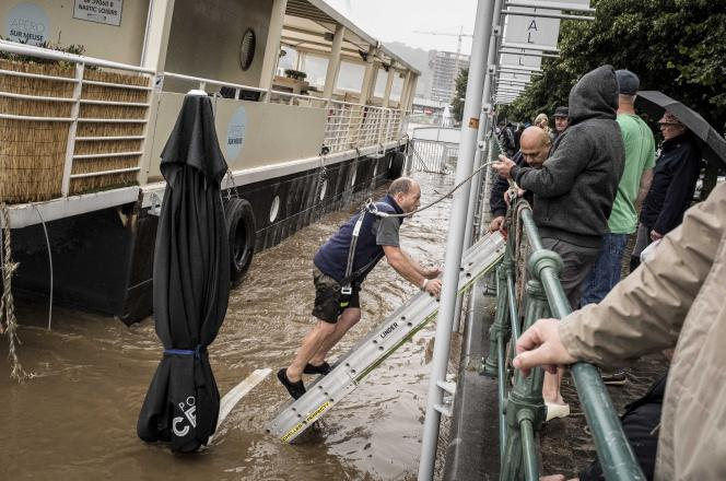 On Thursday, July 15, 2021, a man descends a ladder into the water in an attempt to free his boat at the Muse in Liege, Belgium.