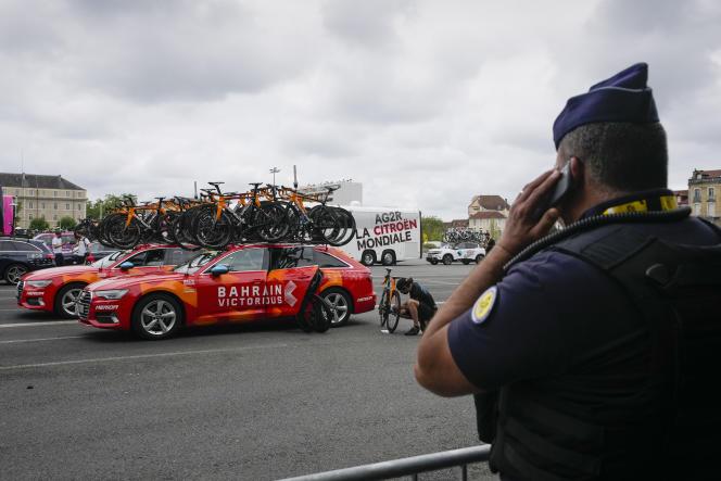 Un gendarme surveille les voitures de l'équipe Bahrain Victorious avant le départ de la 18e étape du Tour de France, à Pau (Pyrénées-Atlantiques), le 15 juillet 2021.