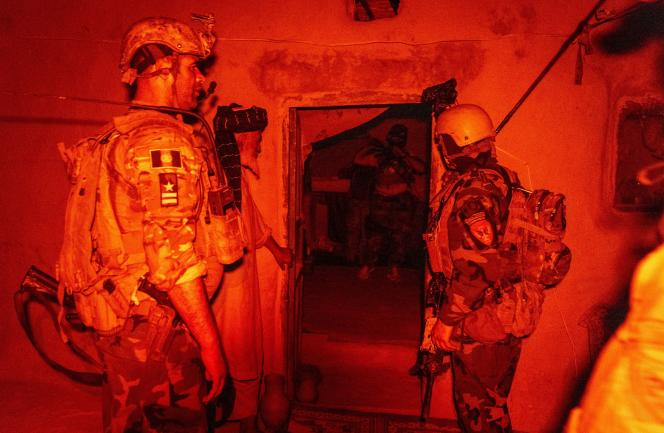 Un membre des forces spéciales afghanes parle à un habitant, tandis que d'autres soldats fouillent sa maison au cours d'une mission contre les talibans, dans la province de Kandahar, en Afghanistan, le 12 juillet 2021.