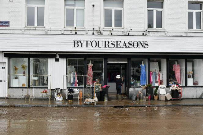 Une personne nettoie l'entrée d'un magasin après qu'il a été dévasté par les eaux, dans le quartierChênée, à Liège (Belgique), le 16 juillet 2021.