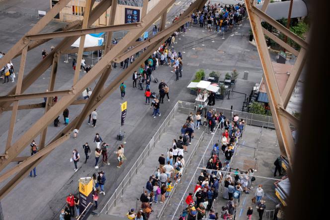 Des visiteurs patientent pour accéder à la tour Eiffel, à Paris, vendredi 16 juillet 2021.