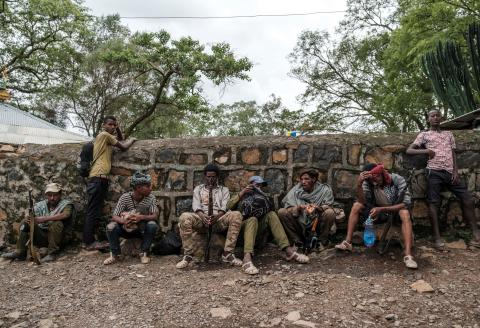 """Members of the Amhara militia rest next to a wall in the village of Adi Arkay, 180 kilometers northeast from the city of Gondar, Ethiopia, on July 14, 2021. On Wednesday the Amhara government spokesman Gizachew Muluneh announced that regional special forces and militias would shift to """"attack"""" mode to reverse the recent battlefield gains by the Tigrayan rebels. His statement appeared just hours after Prime Minister Abiy Ahmed, winner of the 2019 Nobel Peace Prize, vowed to """"repel"""" attacks by Ethiopia's enemies. / AFP / EDUARDO SOTERAS"""