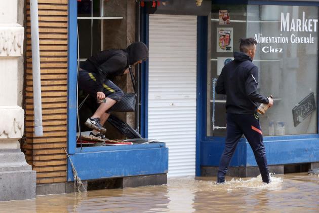 A Verviers, en Belgique, le 15 juillet, certains profitent de la situation pour piller les magasins dont les vitrines ont été brisées par les crues.