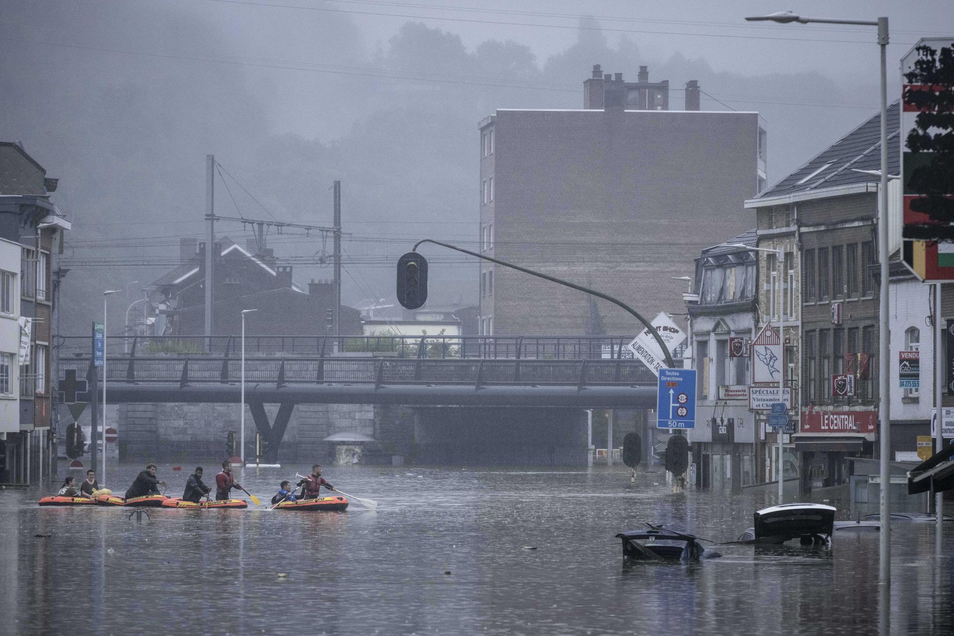 Des habitants de Liège, en Belgique, utilisent des canots pneumatiques pour circuler dans les rues inondées par la Meuse, le 15 juillet 2021.