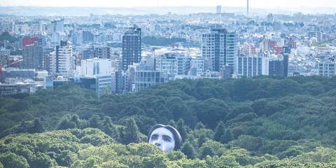 """A hot air balloon created by Japanese art group """"mé"""" pops up over the trees at Tokyo's Yoyogi Park on July 16, 2021, part of a project called """"Masayume"""" - a Japanese word for a dream that becomes reality. - RESTRICTED TO EDITORIAL USE - MANDATORY MENTION OF THE ARTIST UPON PUBLICATION - TO ILLUSTRATE THE EVENT AS SPECIFIED IN THE CAPTION / AFP / Charly TRIBALLEAU / RESTRICTED TO EDITORIAL USE - MANDATORY MENTION OF THE ARTIST UPON PUBLICATION - TO ILLUSTRATE THE EVENT AS SPECIFIED IN THE CAPTION"""