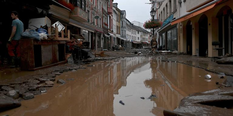 TOPSHOT - A resident stands next to damaged furnitures in a flooded street in Ahrweiler-Bad Neuenahr, western Germany, on July 15, 2021.  German authorities said late July 15, 2021 that at least 58 people had likely died in massive storms and flooding in the country's west, an increase on the earlier toll of 45 dead. / AFP / Christof STACHE
