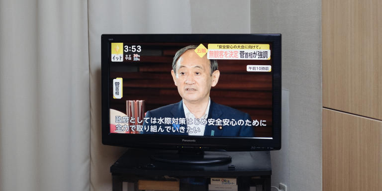 At the living of Konomi's home with TV news about Tokyo Olympic..  The man in a screen is a prime minister, Yoshihide Suga.