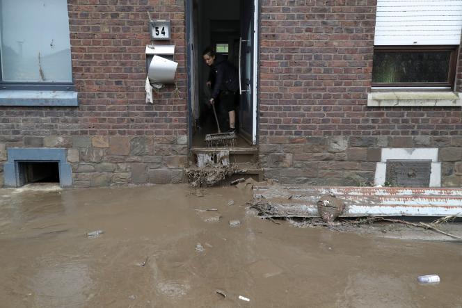 Une femme balaie l'eau de sa maison inondée, après de fortes pluies, à Trooz, en Belgique, le 16 juillet 2021.