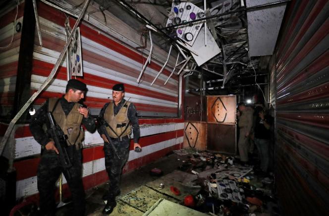 Des forces irakiennes inspectent le lieu d'une explosion, sur un marché de Sadr City, le 19 juillet 2021.