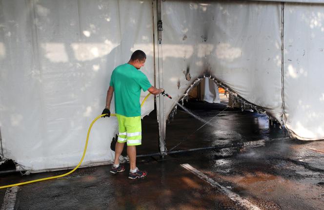 Un employé municipal nettoie le chapiteau du centre de vaccination d'Urrugne, incendié au cours du week-end.
