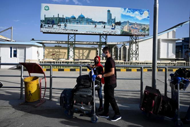 Des proches de ressortissants afghans travaillant avec des organisations françaises et l'ambassade de France vérifient leur nom dans une liste avant de quitter l'Afghanistan sur un vol spécial pour la France, à l'aéroport international Hamid Karzai de Kaboul, le 17 juillet 2021.