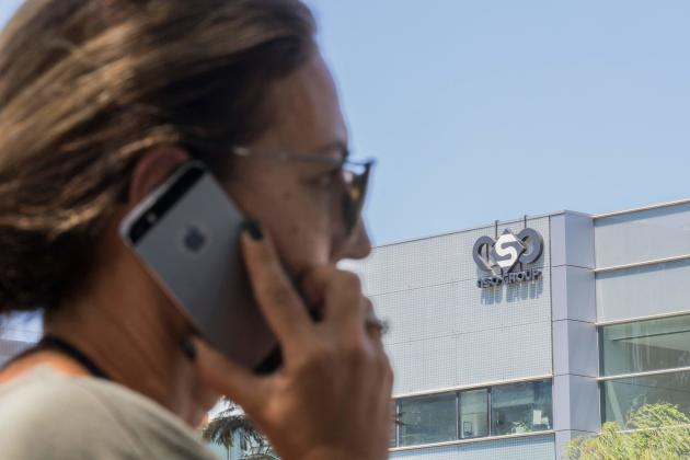 A woman uses her iPhone outside the headquarters of the Israeli company NSO Group in Herzliya on August 28, 2016.