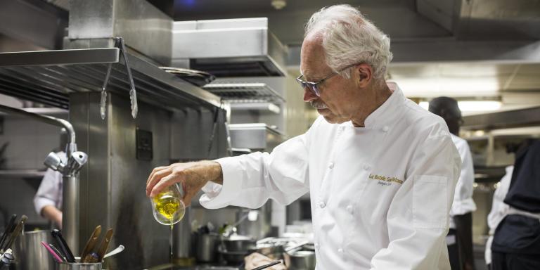 Jacques Chibois dans sa cuisine de la Bastide Saint Antoine, avec le flacon d'huile d'olive emblème de l'établissement. Grasse, juillet 2021
