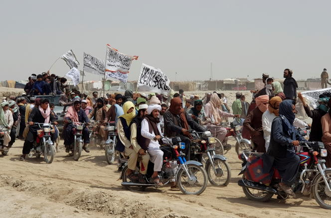 Rassembleme de personnes tenant des drapeaux talibans, près du point de passage de Friendship Gate, dans la ville frontalière pakistano-afghane de Chaman, au Pakistan, le 14 juillet 2021.