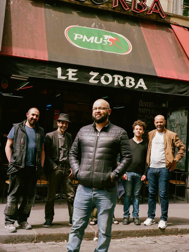 Rabah Becheur, patron du Zorba, devant des employés et habitués du Zorba, dans le quartier de Belleville, à Paris, le 28 mai 2021.