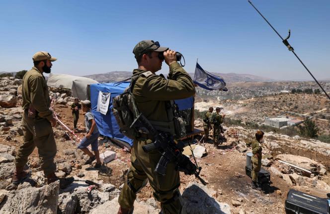 Des soldats israéliens observent le village palestinien de Beita, alors que les colons évacuent la colonie d'Eviatar, en Cisjordanie, le 2 juillet 2021.
