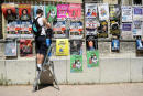 A man hangs play posters in the streets of Avignon on the first day of this year edition of the Avignon theatre festival on July 5, 2021. / AFP / Nicolas TUCAT