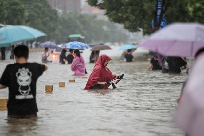 Residentes de la ciudad de Zhengzhou, capital de Henan, China, caminan por las calles inundadas después de las fuertes lluvias del 20 de julio de 2021.