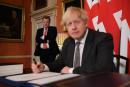 (FILES) In this file photo taken on December 30, 2020 UK chief trade negotiator, David Frost (L) looks on as Britain's Prime Minister Boris Johnson signs the Trade and Cooperation Agreement between the UK and the EU, the Brexit trade deal, at 10 Downing Street in central London. The UK government on July 21, 2021 demanded the EU re-negotiate post-Brexit trading arrangements for Northern Ireland after rioting and business disruption hit the restive province. (Photo by Leon Neal / POOL / AFP)