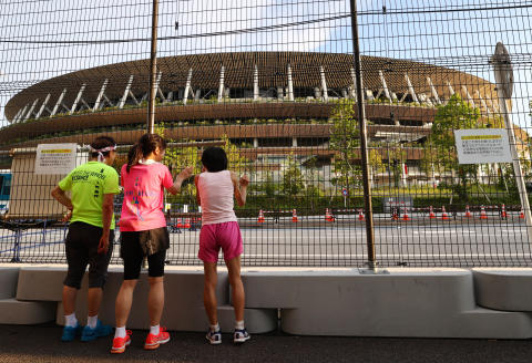 Tokyo 2020 Olympics Preview - Tokyo, Japan - July 22, 2021 Joggers look at the Olympic Stadium REUTERS/Kim Kyung-Hoon