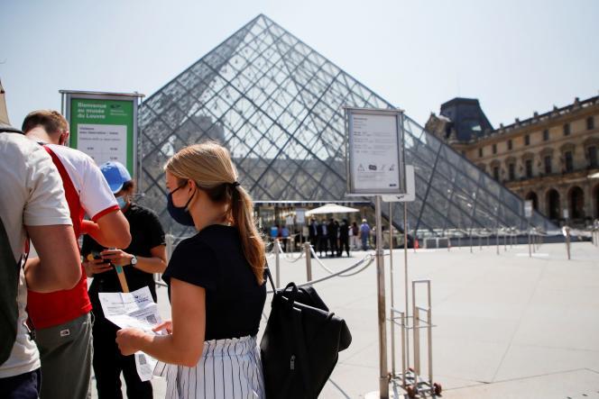 Des visiteurs munis de passes sanitaires devant l'entrée du Musée du Louvre à Paris,le 21 juillet 2021.
