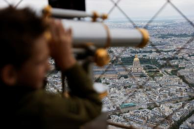 A young boy looks at a monument from the iconic Eiffel Tower as it reopens its doors to tourists since late October 2020, after the second national COVID-19 lockdown in Paris, France, July 16, 2021. REUTERS/Pascal Rossignol