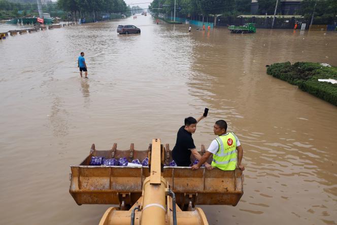 Un chargeur frontal transporte des habitants et des ravitaillements en eau dans une rue inondée à Zhengzhou, dans la province de Henan, en Chine, le 23 juillet 2021.