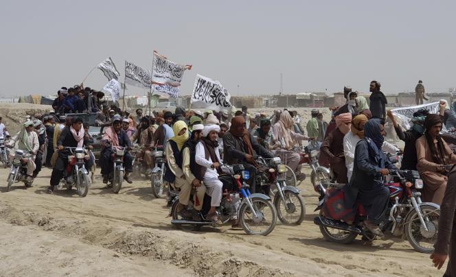 Des Afghans qui soutiennent les talibans portent leur drapeau blanc emblématique à Spin Boldak, le 14 juillet 2021.