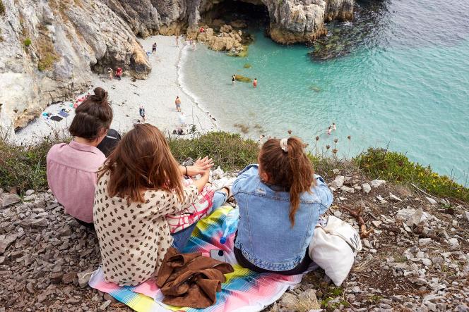 Touristes surplombant la plage sauvage de l'ile vierge sur la presqu'île de Crozon (Finistère), en août 2019.