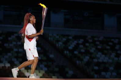 Japanese tennis player Naomi Osaka holds the Olympic Torch before lighting the flame of hope in the Olympic Cauldron during the opening ceremony of the Tokyo 2020 Olympic Games, at the Olympic Stadium, in Tokyo, on July 23, 2021. (Photo by HANNAH MCKAY / POOL / AFP)
