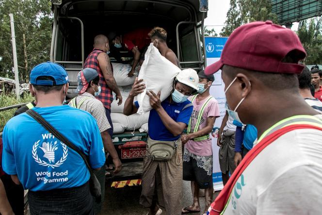 Des personnes reçoivent des sacs de riz distribués par le Programme alimentaire mondial, dans la périphérie de Rangoun, en Birmanie, le 21 mai 2021.